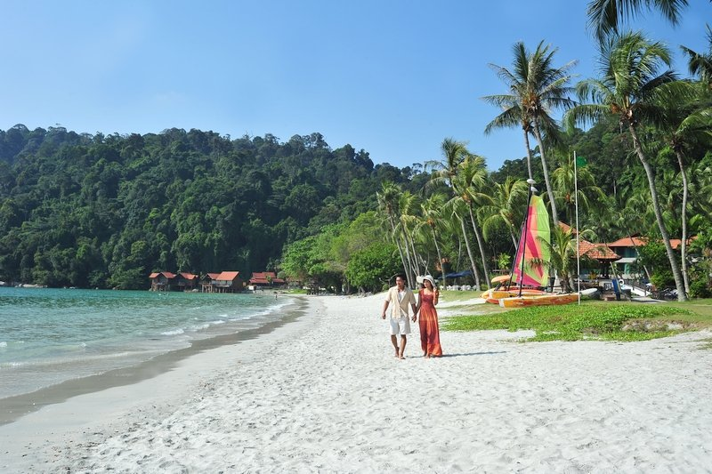 A couple of Tourists walking on a tranquil beach in Pangkor Island