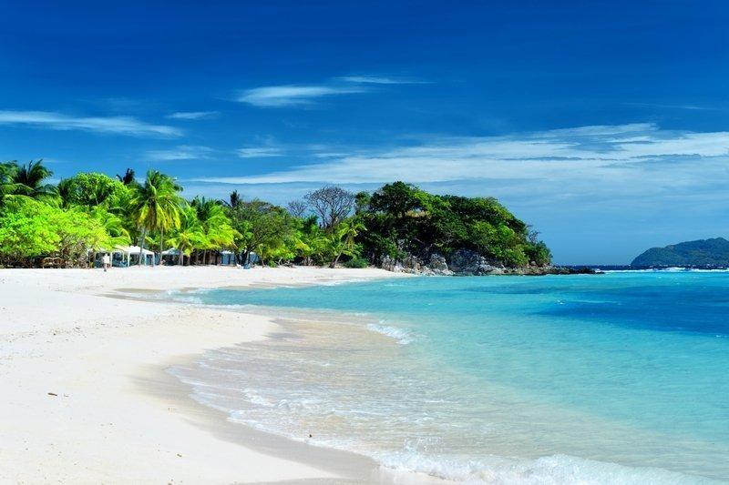 Perfect white sand beach and turquoise tropical sea in Malcapuya Island