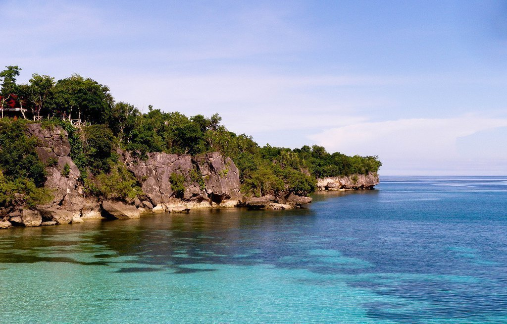 Rocky coastline and calm blue sea in Siquijor island