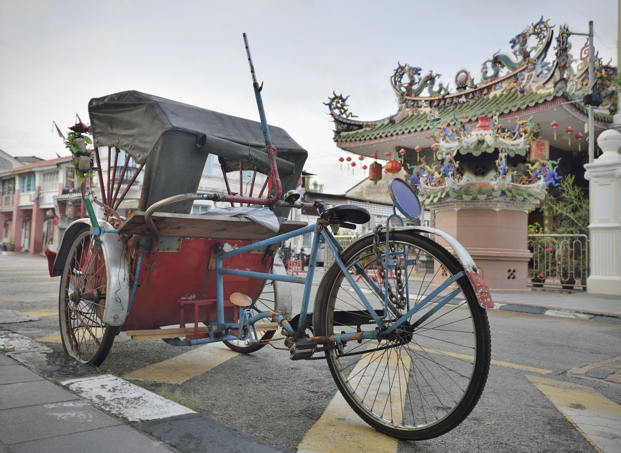Traditional rickshaw and Chinese temple in George Town Penang.