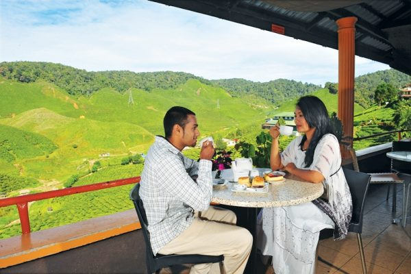 A couple of Tourists enjoying a cup of tea at the panoramic terrace overlooking the Cameron Highlands Tea Plantations