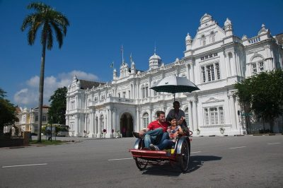 A couple of Tourists enjoying a Trishaw Ride in Georgetown Penang