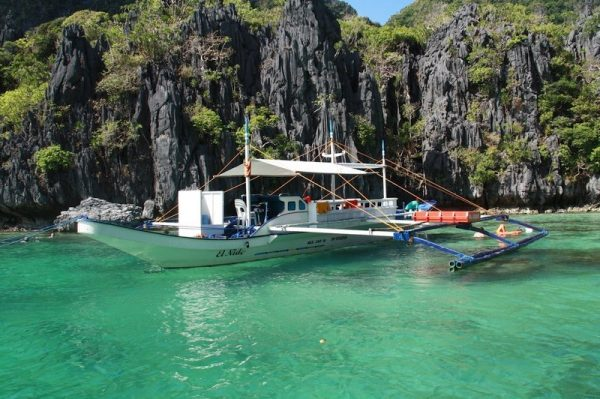 A boat floating on the emerald water of El Nido's Miniloc Island