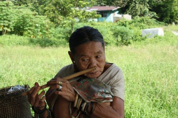 Penan woman playing a flute in Mulu National Park