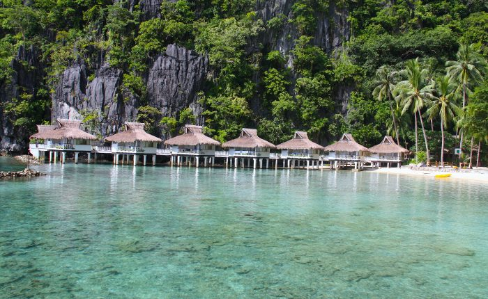Bungalows over-the-water overlooking the lagoon in front of Miniloc Island's El Nido Resorts